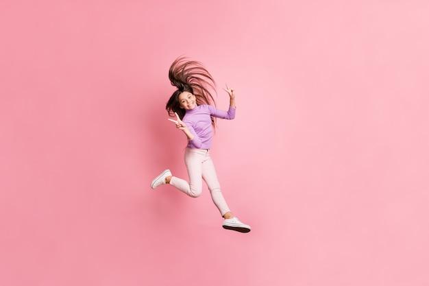 어린 소녀 점프의 전신 사진은 파스텔 색상 배경 위에 격리된 v-sign을 바이올렛 스웨터로 만듭니다.