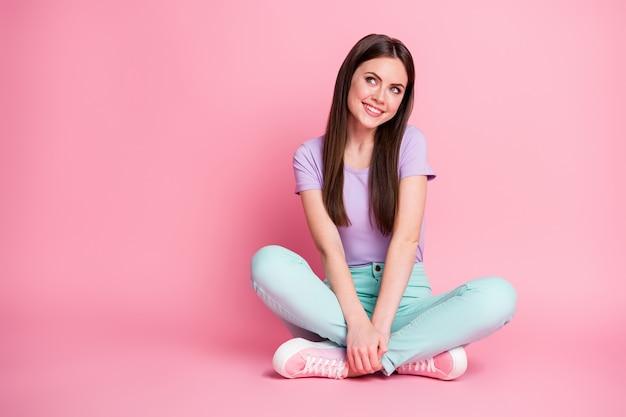 Полное фото прекрасной милой девушки, сидящей на полу, скрещенными ногами, взгляд, одетый в фиолетовый наряд copyspace, изолированный на розовом цветном фоне