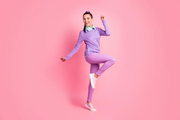 Фотография всего тела милой возбужденной девушки стоит изолированной на розовом пастельном цветном фоне и наслаждается фиолетовой одеждой