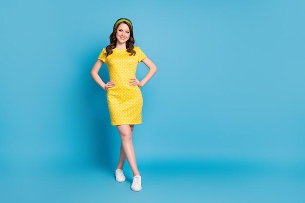 素敵な甘い女の子の全身写真スタンド空のスペースを入れて手を腰に着用水玉模様のスカートを青い色の背景の上に分離