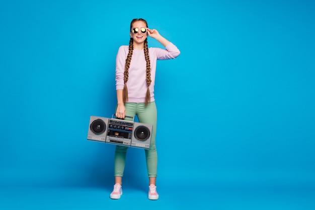 머리띠 땋은 머리 소녀와 현대 청소년의 전신 사진은 복고풍 붐 박스를 잡고 봄 휴가에 미친 원하는 파티를 느끼고 분홍색 스웨터 운동화 녹색 바지 바지 격리 된 파란색 배경을 착용