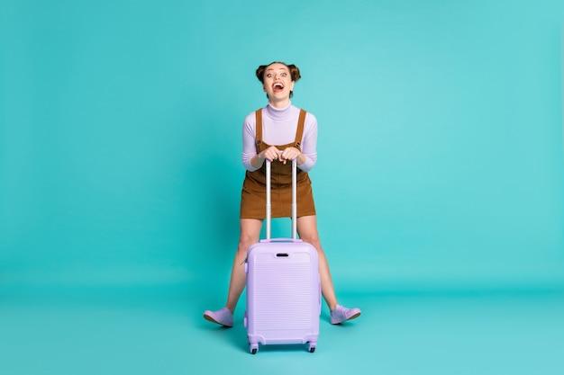 유치한 행동을 하는 장난기 어린 소녀의 전신 사진 국제 터미널 체크인은 짧은 트렌디한 갈색 드레스 바이올렛 운동화 스웨터 격리된 청록색 배경