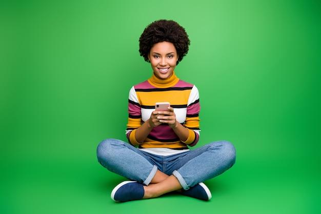 Фотография всего тела позитивной афро-американской девушки-блогера, сидящей, скрестив ноги, сложена, пользуется смартфоном, читаю новости соцсети, расслабляешься в чате, носишь сияющий наряд