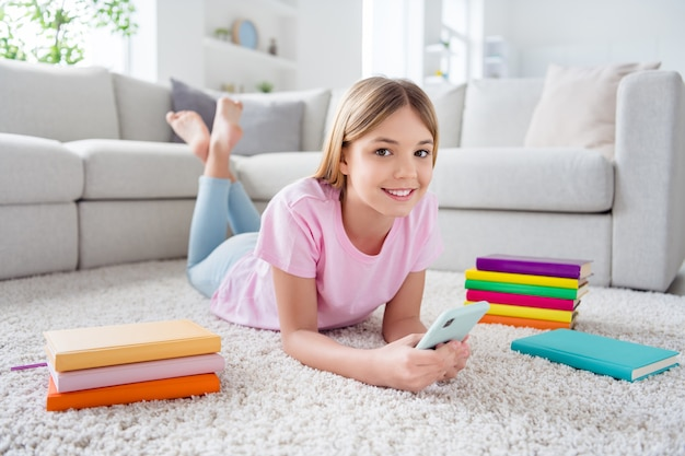 Полное фото тела позитивной девочки, лежащей на ковре на полу, использует мобильный телефон, наслаждается общением в социальных сетях, репост подписывается в доме в помещении