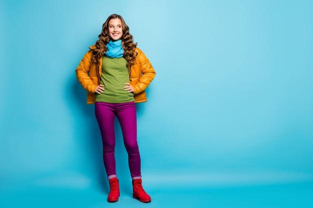 かなり巻き毛の女性の全身写真は春の晴れた日をお楽しみくださいストリートルックサイド空のスペースを着用カジュアルな黄色のオーバーコートスカーフ紫のズボン赤い靴孤立した青い色の壁