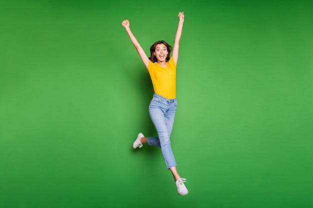 Фотография всего тела довольно забавно прыгающего марафона с высоким бегом, подняв руки, занявшего первое место