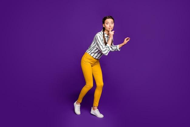 Полное фото красивой дамы, держащей палец на губах, идущей на цыпочках, неожиданный неожиданный визит, одетая в полосатую рубашку, желтые брюки, изолированный фиолетовый цвет фона