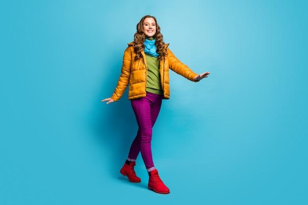 Фото в полный рост симпатичной путешественницы, идущей по улице за границей, хорошее настроение в желтом пальто, шарфе, фиолетовых брюках, зеленом джемпере, красных туфлях, изолированной синей стене