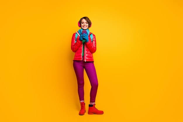 探している電話のオンラインマップを使用して通りを歩いているきれいな女性の全身写真はカジュアルな赤いコートのブーツを着用します青いスカーフ手袋耳カバーパンツ