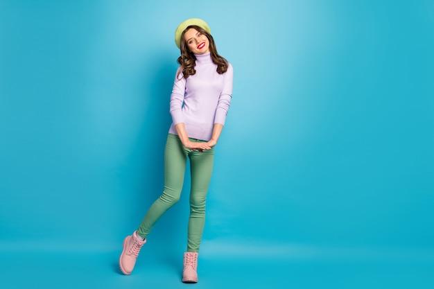 Фото в полный рост симпатичной дамы стильный внешний вид хорошее настроение гулять по улице за границей носить современный зеленый берет шляпа фиолетовый водолазка джемпер брюки туфли изолированно синий цвет стена
