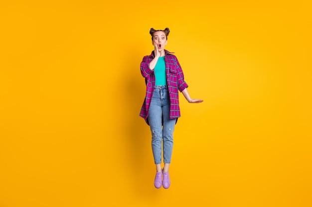 かなり素敵なショックを受けた10代の女性の全身写真は興奮して高くジャンプします驚くべき信じられないほどのニュースを聞くカジュアルな格子縞のシャツスニーカージーンズ分離された黄色の鮮やかな輝きの色の背景