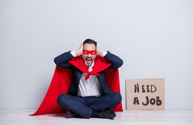 ストレスのたまったクレイジー成熟した解雇されたビジネスの男のスーパーヒーローの衣装の全身写真座る床プラカード耳に必死の腕を叫ぶスーツ赤いフェイスマスクマント分離された灰色の背景