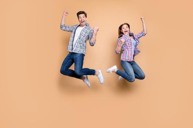 Фотография всего тела двух человек сумасшедшая леди парень прыгает высоко, празднуя лучшую победу, поднимая кулаки, распродажа, торговые новости, повседневная клетчатая джинсовая одежда, изолированный бежевый фон