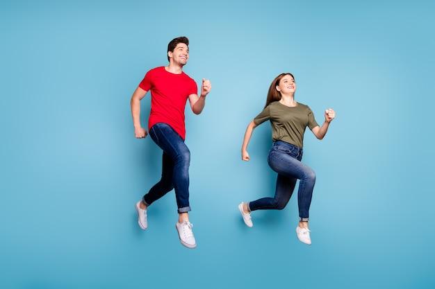 Фотография всего тела двух супругов расслабиться, отдохнуть, прыгать, бегать, носить одежду в повседневном стиле, изолированную на синем цветном фоне