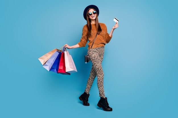 Full body photo of positive boutique client girl enjoy off-sales shopping weekends hold bargains bags hold easy payment credit card wear brown pants retro hat isolated blue color wall