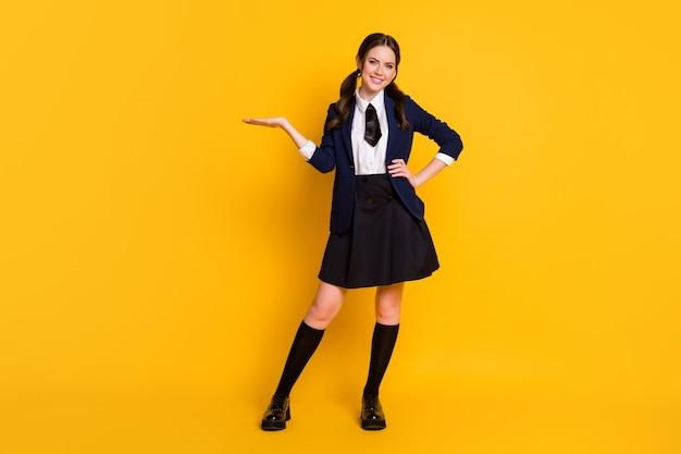 Full body photo of positive smart teenager university teacher hold hand display ads