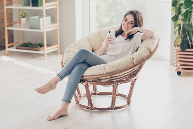Full body photo of positive young girl sit armchair use smartphone wear casual style clothes in house indoors