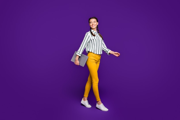 Full body photo of pretty business lady freelancer holding notebook hands walking students lecture class wear striped shirt yellow trousers isolated purple color background