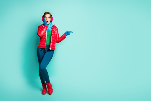Full body photo of pretty lady indicate fingers empty space showing sale prices hand on cheek wear red overcoat blue scarf pink ear muffs pants shoes isolated teal color wall