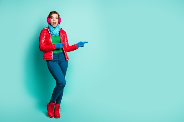 Full body photo of pretty lady indicating fingers empty space proposing sale prices black friday wear red overcoat blue scarf pink ear muffs pants shoes isolated teal color wall