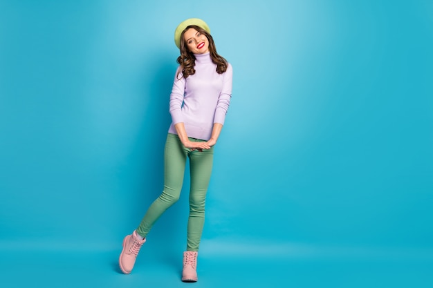 Full body photo of pretty nice lady stylish look good mood walk street abroad wear modern green beret hat purple turtleneck jumper pants shoes isolated blue color wall