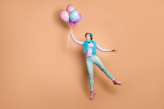 Full body photo of pretty shocked lady jump high hold many air balloons raise up with wind blow wear violet jumper green pants boots blue beret scarf isolated beige color background