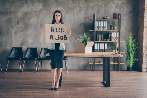 Full body photo of upset sad girl lose job company covid crisis bankrupt hold cardboard text wear blazer suit high-heels in workplace workstation