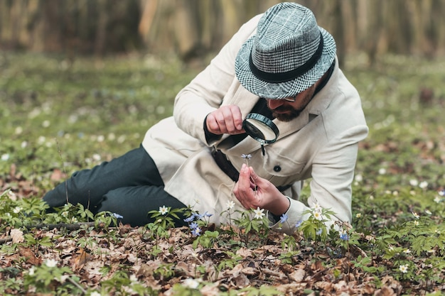 Full-body pic of elegant-looking man studying flower through magnifier lying on ground in nature
