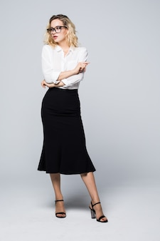 Full body picture of a happy young business woman standing on white wall