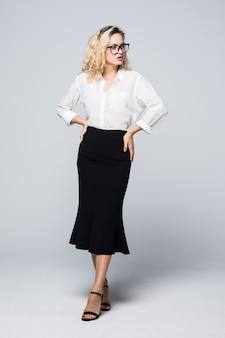 白い壁に立っている幸せな若いビジネス女性の全身写真