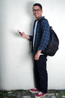 Full body portrait of asian man smiling holding mobile phone