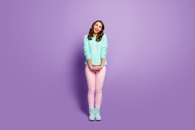 Full body portrait of beautiful pretty lady curly hairstyle good mood look up empty space dreamer wear fluffy pastel sweater pink pants shoes.