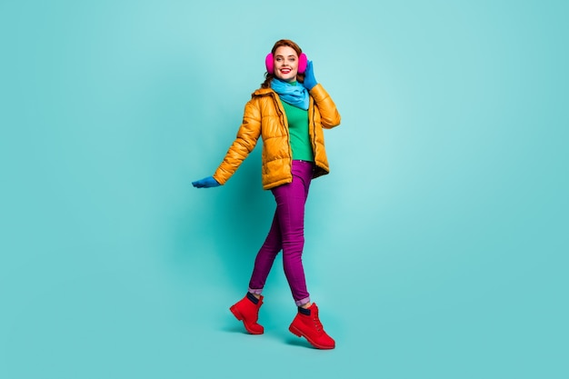 Full body portrait of content candid woman enjoy winter autumn weekend go walk touch ear warmers wear pink red bright boots.