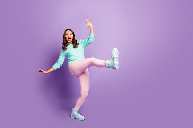 Full body portrait of crazy pretty wavy lady raise one leg strange weird youth dancing moves students party wear fluffy pastel pullover pink pants footwear.