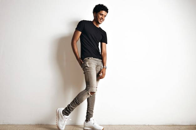 Full body portrait of a cute tall young african american model with an afro in a plain black cotton t-shirt, white sneakers and slim grey jeans isolated on white