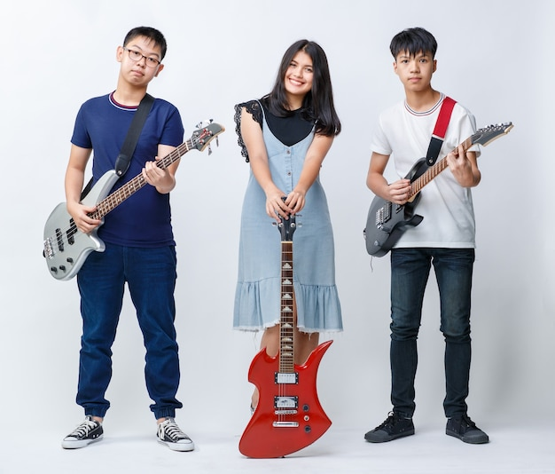 악기를 들고 흰색 배경의 카메라를 바라보는 세 명의 10대 음악가의 전신 초상화 그룹 샷. 어린 소년과 소녀 베이시스트와 기타리스트의 그룹 샷. 밴드의 개념