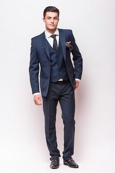 孤立した白い壁に立っているスーツを着たビジネスマンの全身肖像画