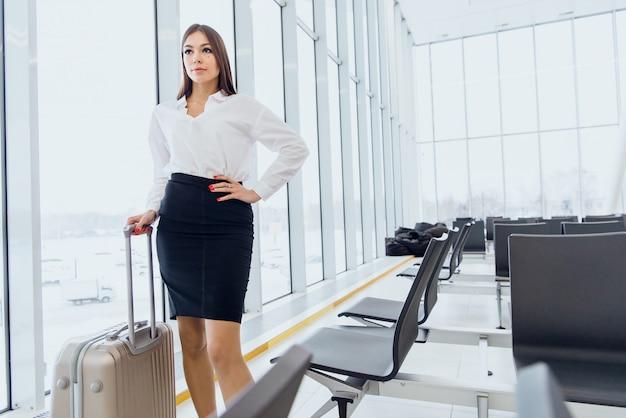 空港でスーツケースを持って歩いて幸せなビジネス女性の全身肖像画
