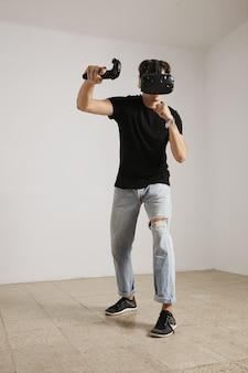 Vr 안경과 청바지를 입은 젊은 게이머의 전신 초상화와 흰색 벽과 밝은 나무 바닥이있는 방에서 게임을하는 검은 색 라벨이없는 티셔츠.