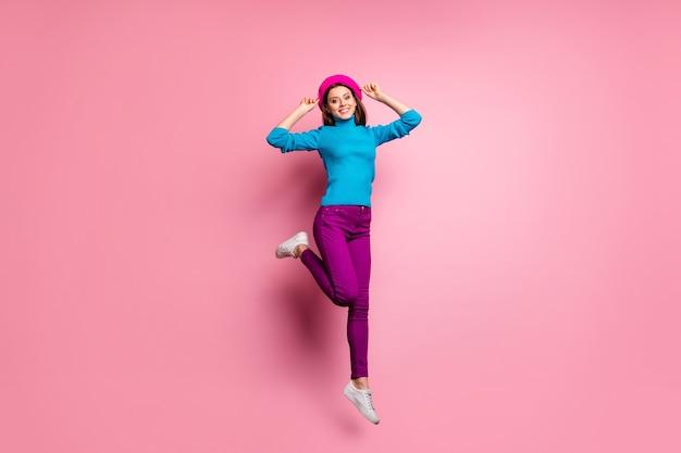 매력적인 명랑 소녀 점프의 전신 초상화는 주말을 만지면 서 모던 한 프렌치 베레모를 만지면 서 세련된 옷을 입고 감정을 느끼게한다.