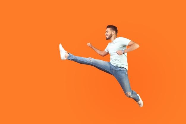 Полный портрет возбужденного брюнет с бородой в кроссовках и джинсовой одежде, перепрыгивающего в воздухе, быстро бегущего, спешащего за скидками. закрытый студийный выстрел изолирован на оранжевом фоне
