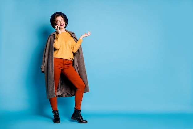 電話の友人を話すきれいな女性旅行者の全身の肖像画は、アドレスショッピングセンターの摩耗シーズンの長い灰色のコートのプルオーバーズボンの帽子の靴を伝えます。