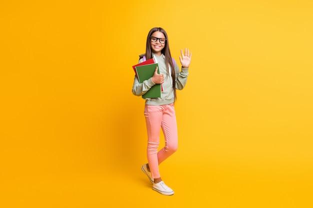 Полное тело портрет студента носить рюкзак волна рука стильная толстовка с капюшоном, изолированные на фоне желтого цвета