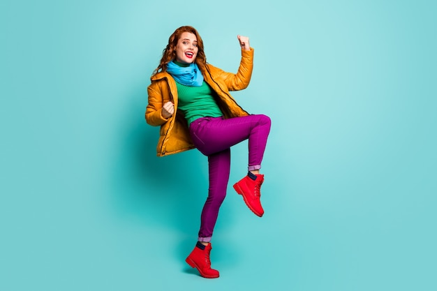 Full body portrait of pretty lady raise fists celebrate successful achievement wear trendy casual yellow overcoat scarf violet trousers shoes.