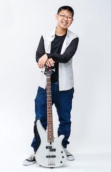 ベースギターを持っているかわいい笑顔の少年ティーンエイジャーの全身ポートレートショット。カメラの孤立した白い背景を見ながら立って楽器を演奏するプロのジュニアベーシスト