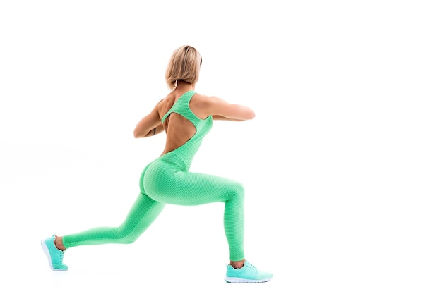 Full body portrait of unknown young sporty woman stretching