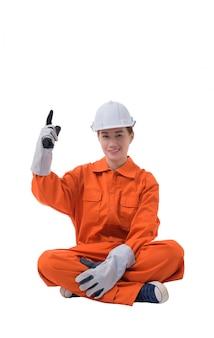 Full body portrait of a woman worker in mechanic jumpsuit is sitting finger up
