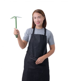 Full body portrait of a worker woman or servicewoman in gray shirt and apron is holding shovel for cultivators on white background