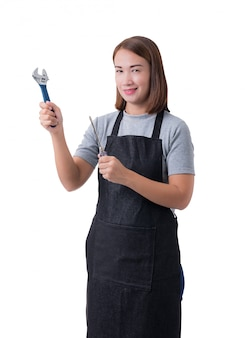 Full body portrait of a worker woman or servicewoman in gray shirt and apron is holding wrench