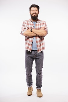 Full body portrait of young casual man smiling, isolated on white wall